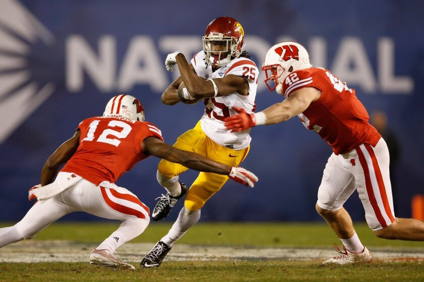 USC's Ronald Jones II runs through the defense of Wisconsin's Natrell Jamerson, left, and T.J. Watt during the Holiday Bowl in San Diego on Dec. 30, 2015.
