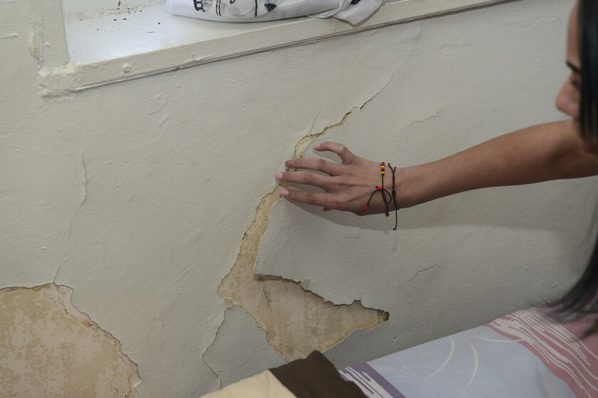 Norma Concepcion shows where paint is peeling from walls in almost every room of her home and formin