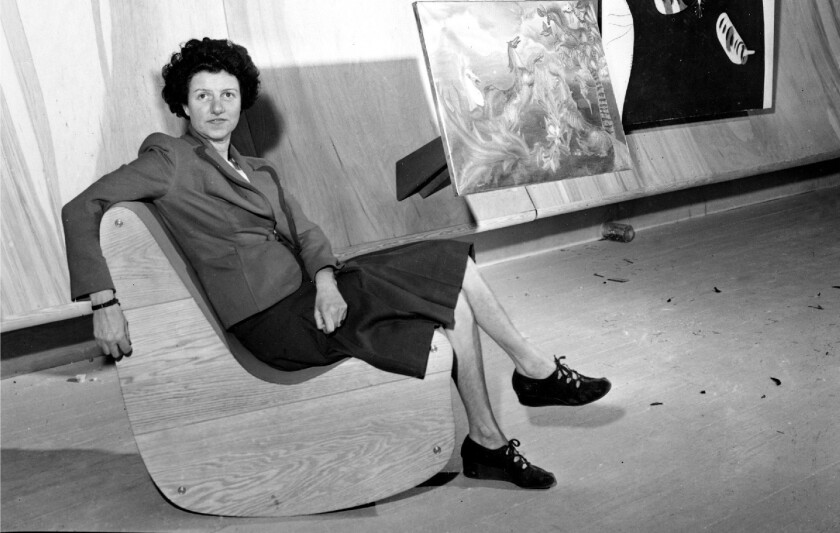 Art collector Peggy Guggenheim poses with paintings at the Museum of Modern Art in New York in 1942.