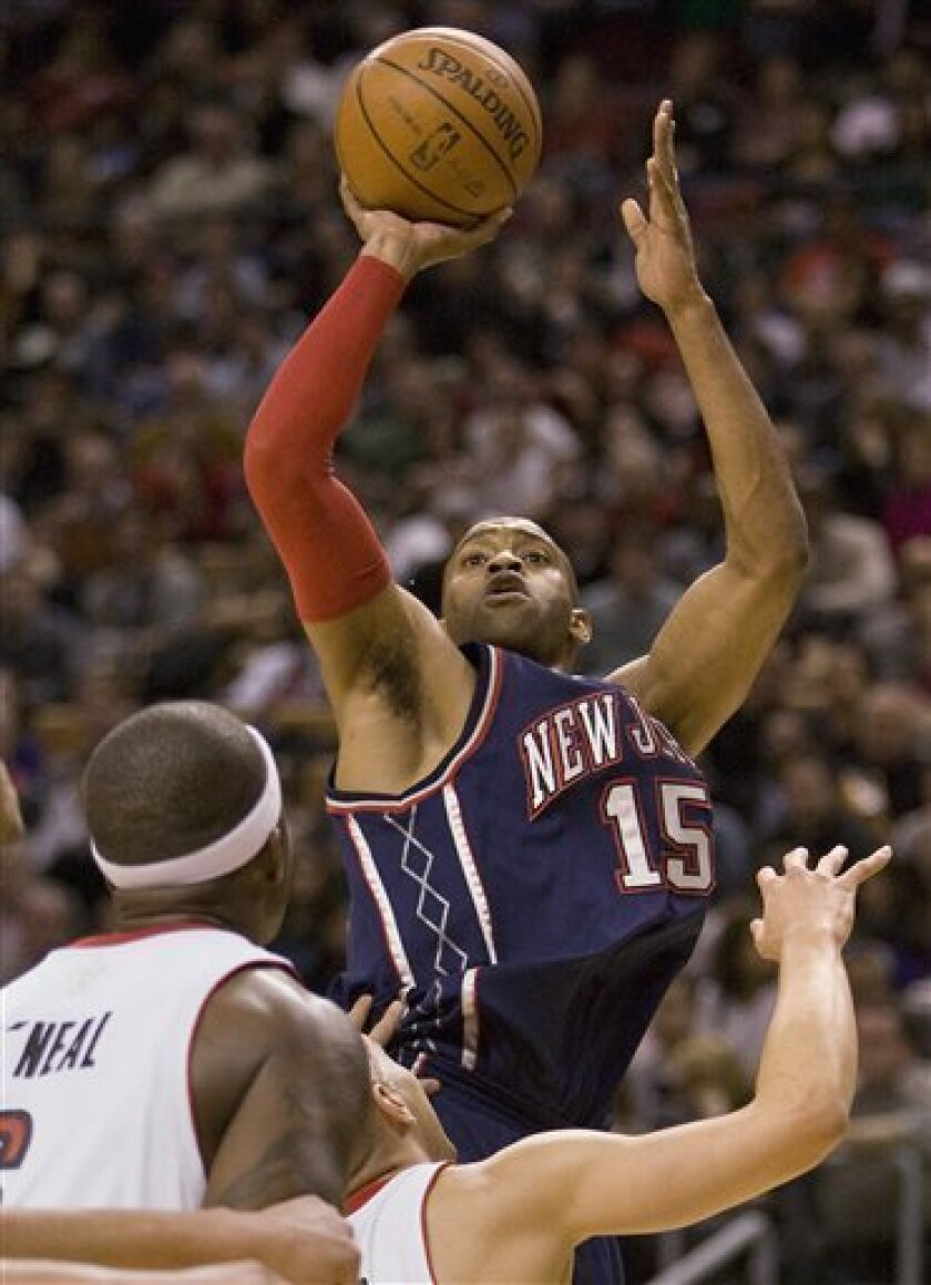 New Jersey Nets guard Vince Carter shoots over Toronto Raptors' Jermaine O'Neal, left, and Anthony Parker during the first half of an NBA basketball game in Toronto on Monday, Dec. 15, 2008. (AP Photo/The Canadian Press, Frank Gunn)