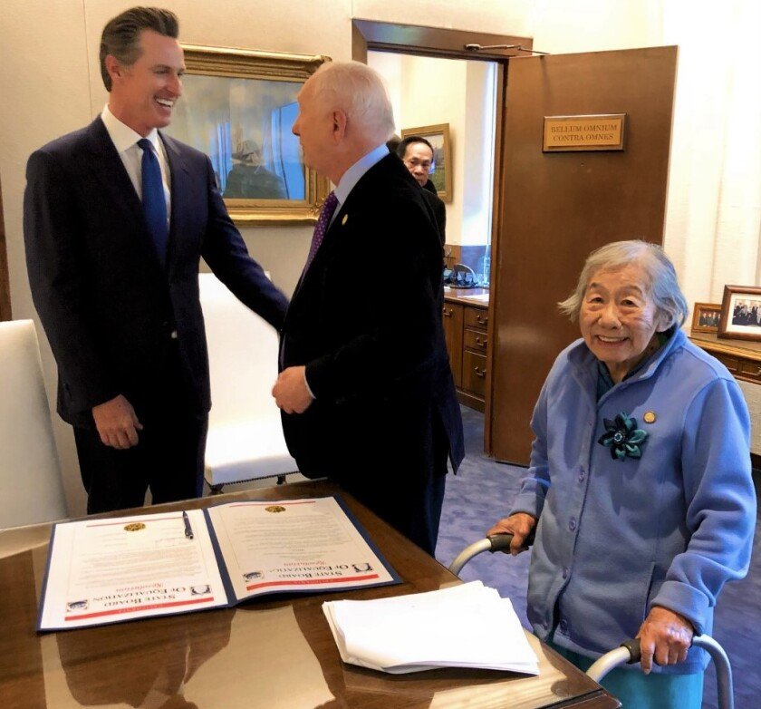 Gov. Gavin Newsom, left, with Mike Schaefer and oldest state employee, May Lee, 99, right.