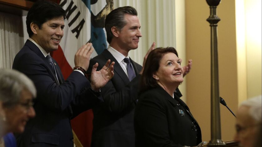State Sen. Toni Atkins (D-San Diego) smiles up at the Senate gallery after being sworn in as the new Senate president pro tem Wednesday. She replaces former Sen. Kevin de Leon (D-Los Angeles), left. In the center is Lt. Gov. Gavin Newsom.