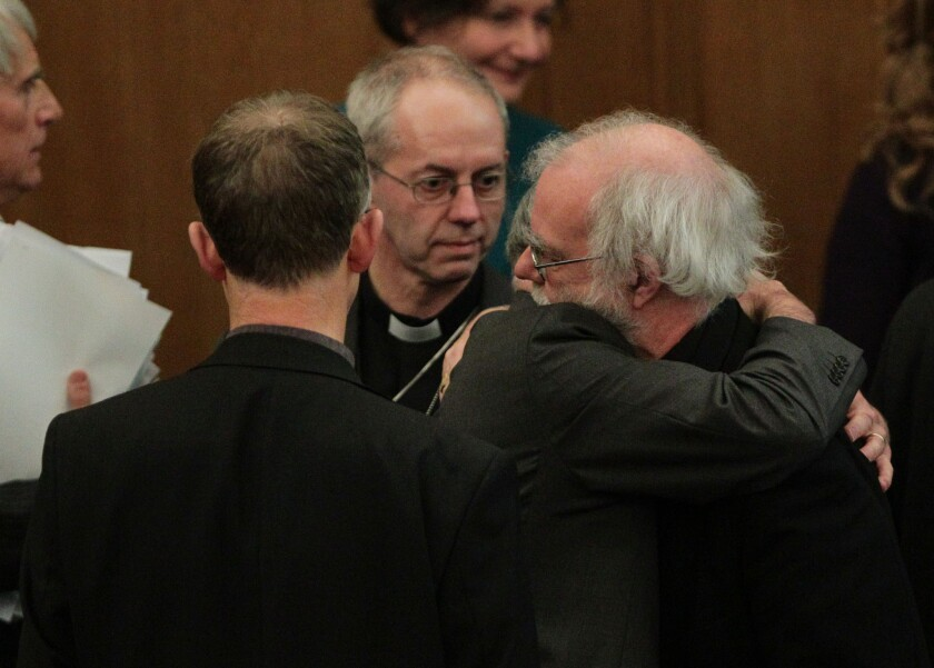 Rowan Williams, the outgoing archbishop of Canterbury, is hugged by a colleague after draft legislation to allow female bishops in the Church of England failed to receive final approval.
