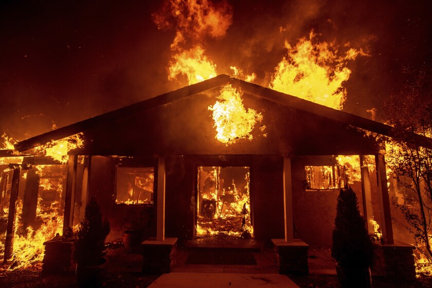 Flames engulf a home in Paradise, Calif., during the Camp fire in 2018.