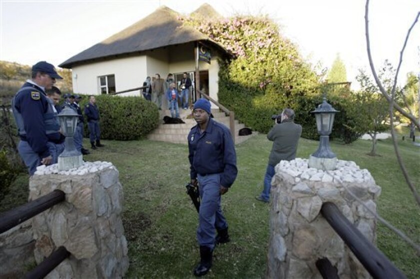 South African police walk around the bungalows of the the Nutbush Loma Lodge near Magaliesburg, outside Johannesburg, Wednesday, June 9 2010. A Portuguese photographer was held up at gunpoint early Wednesday while two other journalists were also robbed at the same World Cup hotel. Spanish journalist Miguel Serrano told The Associated Press that photographer Antonio Simoes was held down in his bed for 30 minutes while two thieves stole camera equipment worth $35,000 (€29,000) early Wednesday at the Nutbush Boma Lodge in Magaliesburg,120 kilometers (75 miles) northwest of Johannesburg. (AP Photo/Miguel Angel Morenatti, Diario AS)