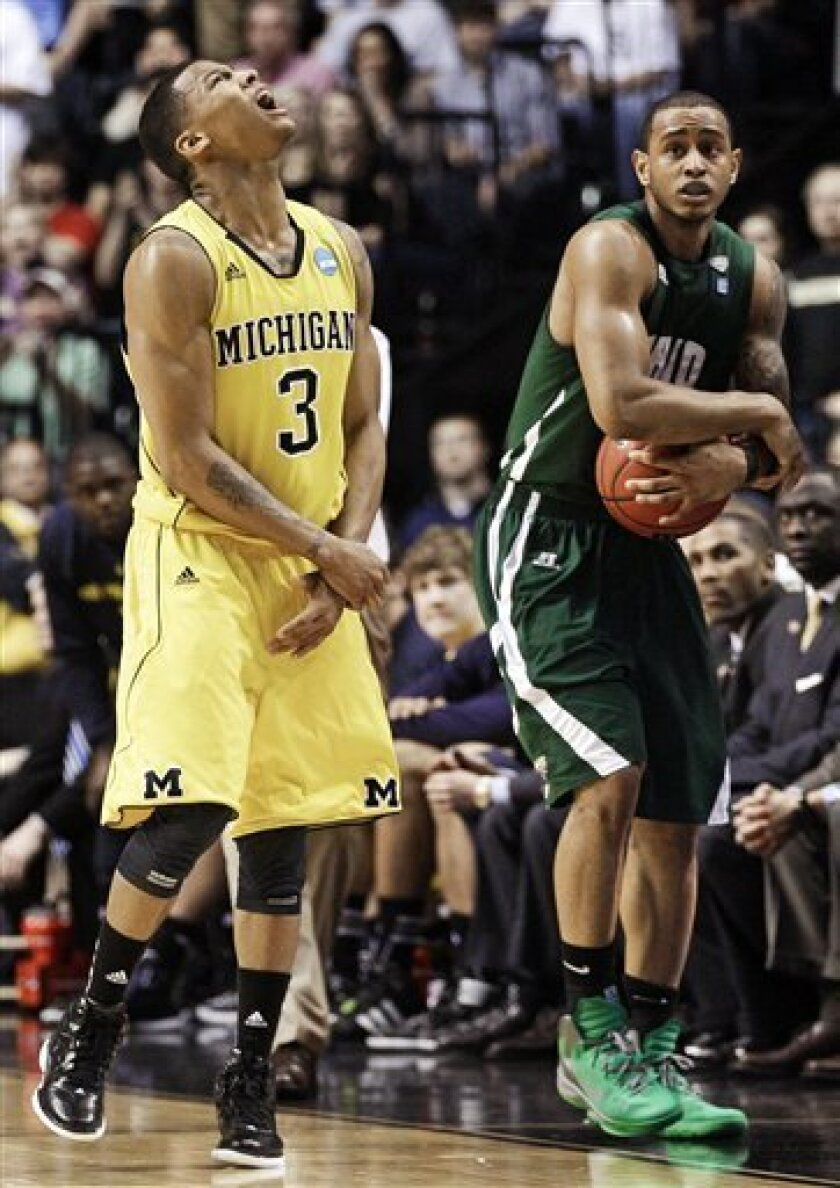 Michigan guard Trey Burke, left, yells as Ohio guard Walter Offutt, right, holds onto the ball after Offutt drew a foul against Michigan in the final seconds of a second-round NCAA college basketball tournament game on Friday, March 16, 2012, in Nashville, Tenn. The resulting free throws by Offutt sealed a 65-60 win for Ohio. (AP Photo/Mark Humphrey)