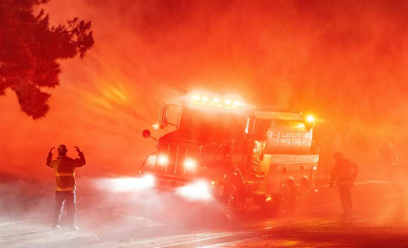 Firefighters spray down flames on the side of Interstate 210 in Sylmar, California.