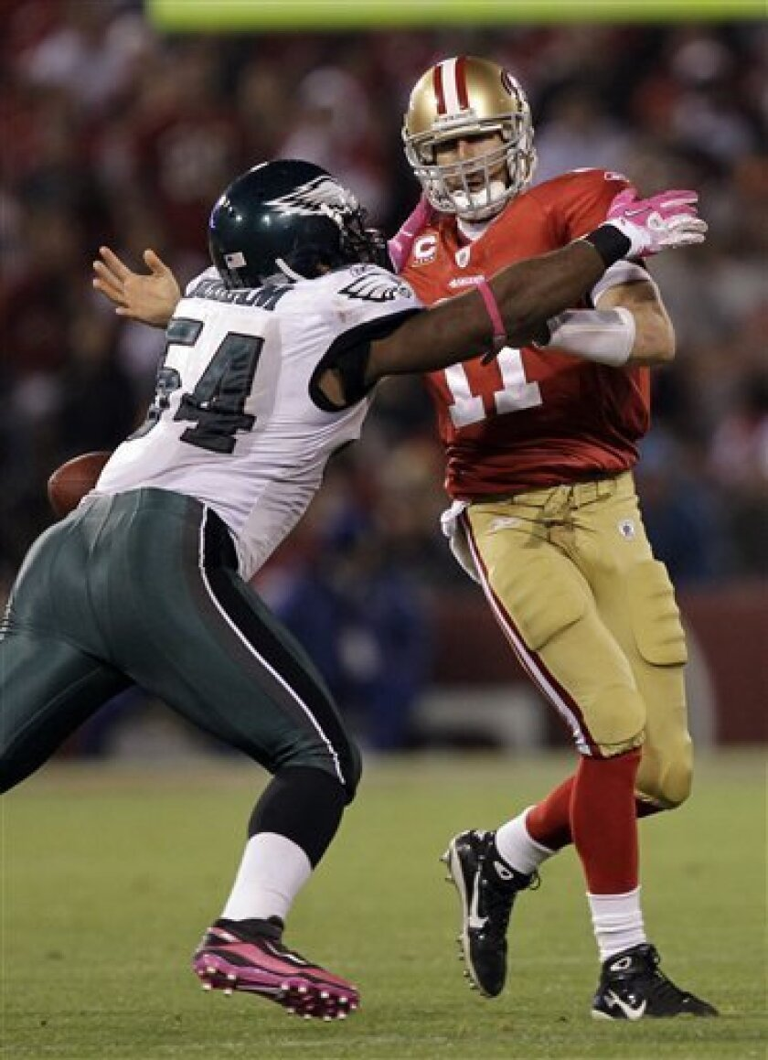San Francisco 49ers quarterback Alex Smith, right, fumbles the ball as Philadelphia Eagles defensive end Brandon Graham, left, defends, during the fourth quarter of their NFL football game in San Francisco, Sunday, Oct. 10, 2010. The fumble led to 52-yard return for a touchdown by Philadelphia Eagles safety Quintin Mikell. (AP Photo/Marcio Jose Sanchez)