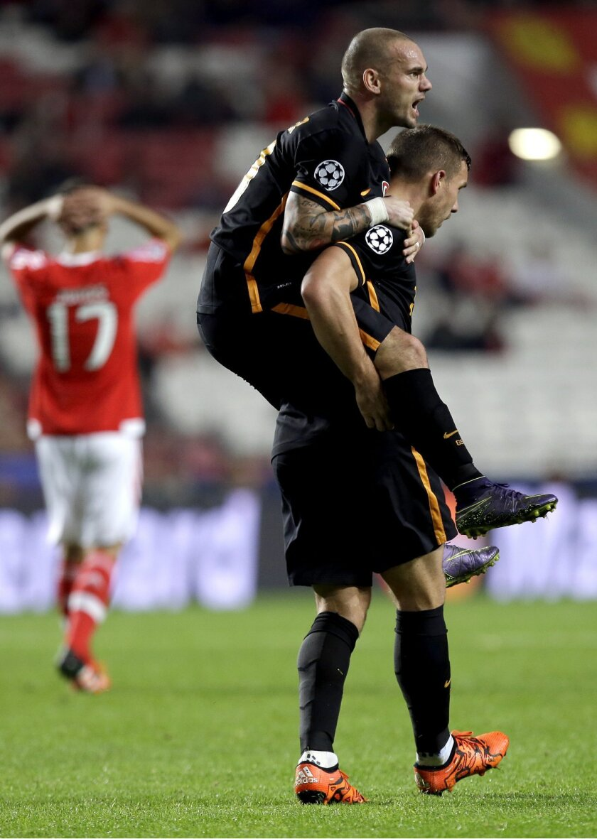 Galatasaray's scorer Lukas Podolski carries teammate Wesley Sneijder as they celebrate their side's first goal during the Champions League group C soccer match between Benfica and Galatasaray at the Luz stadium in Lisbon, Portugal, Tuesday, Nov. 3, 2015.  (AP Photo/Armando Franca)