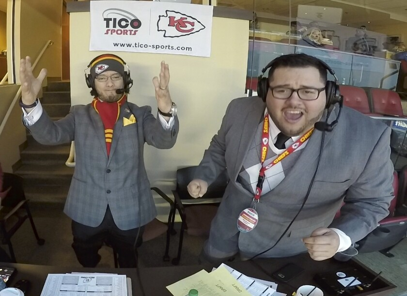 """This Jan. 6, 2018, photo taken from video and provided by Oscar Monterroso, shows Spanish language broadcasters Oscar """"El Tico"""" Monterroso, left, and Enrique """"Kike"""" Morales working at their broadcast booth inside Arrowhead Stadium in Kansas City, Mo., during the Kansas City Chiefs vs Tennessee Titans NFL wild card game. Monterroso, the color commentator, and Morales, the play-by-play man, have been calling Chiefs games in Spanish since 2011, and will broadcast on Saturday, Oct. 5, 2019, Nebraska's NCAA college football game against Northwestern. Nebraska will be the first school in the Big Ten to offer a Spanish-language radio broadcast for a football game. (Oscar Monterroso/Tico Productions via AP)"""