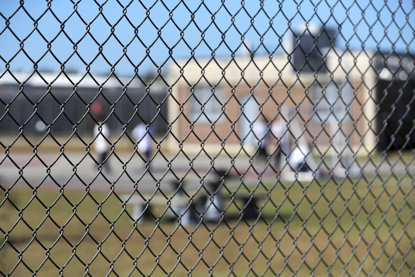 """FILE - In this Sept. 26, 2019 file photo, detainees sit in a yard during a media tour inside the Winn Correctional Center in Winnfield, La. Immigrant advocates sued the Trump administration Tuesday, Dec. 10, 2019 for ending a free hotline that allowed detained immigrants to report concerns about custody conditions after it was featured on the show """"Orange Is the New Black."""" The nonprofit group Freedom for Immigrants, which has run the hotline since 2013 with a free phone line provided by U.S. Immigration and Customs Enforcement, sued in federal court in Los Angeles. (AP Photo/Gerald Herbert, File)"""