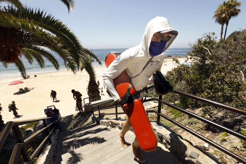 A lifeguard wearing a face covering heads up the steps in Heisler Park in Laguna Beach