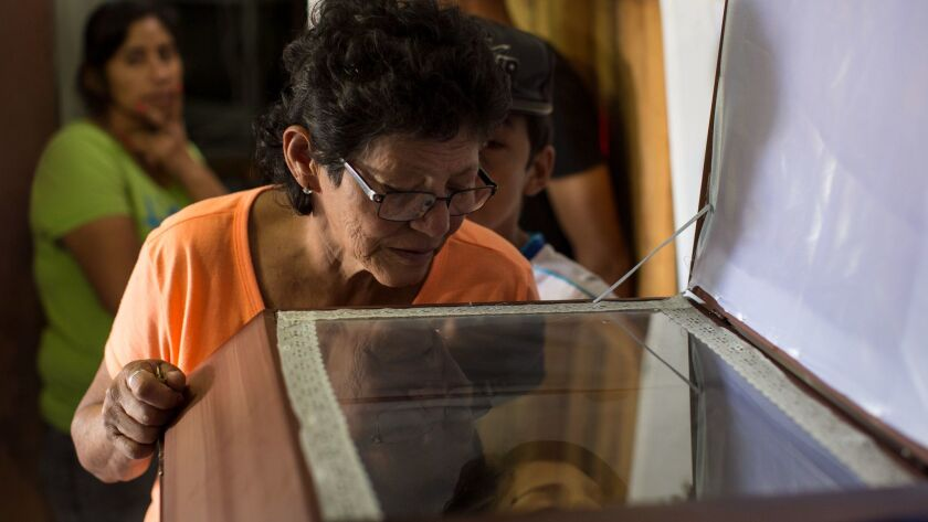 Yolanda Barahona looks into the coffin containing the remains of her granddaughter Kimberly Dayana F