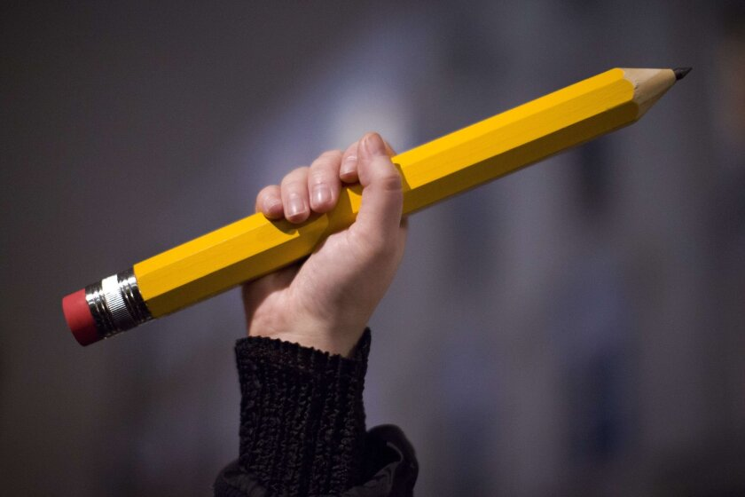 A giant pencil is held at a vigil outside the French Institute in London on Jan. 9 for the 12 victims of the attack on the Paris offices of Charlie Hebdo.