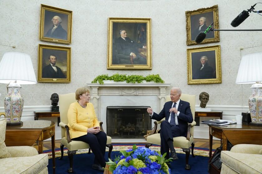 German Chancellor Angela Merkel sits in a chair next to President Biden.