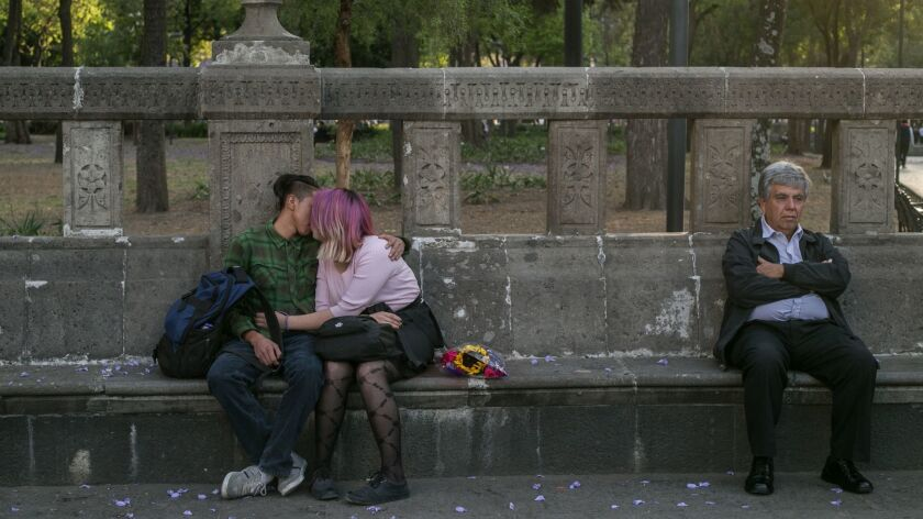 March 22, 2019 - A young couple kisses in Mexico City's Alameda Park. The park, like many public spa
