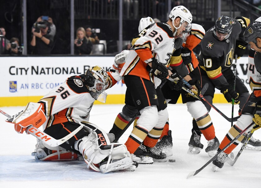 Ducks goalie John Gibson and defenseman Jacob Larsson, center, try to keep the puck out of the net.