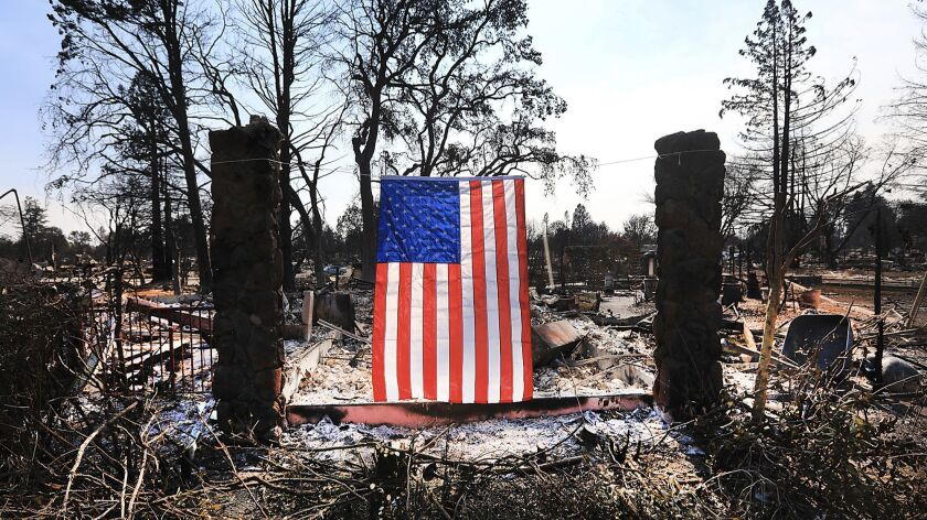 A homeowner displays an American flag amidst the destruction from a wildfire.