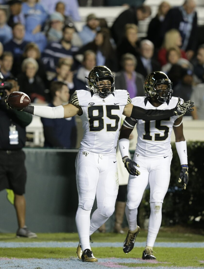 FILE - In this Oct. 17, 2015, file photo, Wake Forest's Cam Serigne (85) celebrates following his touchdown against North Carolina during the first half of an NCAA college football game in Chapel Hill, N.C. Serigne is tired of racking up empty stats at Wake Forest. He's established himself as one of the Atlantic Coast Conference's best tight ends while playing for one of the league's worst teams, and now he's dedicated this offseason to making the Demon Deacons winners again. (AP Photo/Gerry Broome, File)