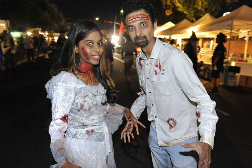 A woman and man dressed as zombies for Halloween