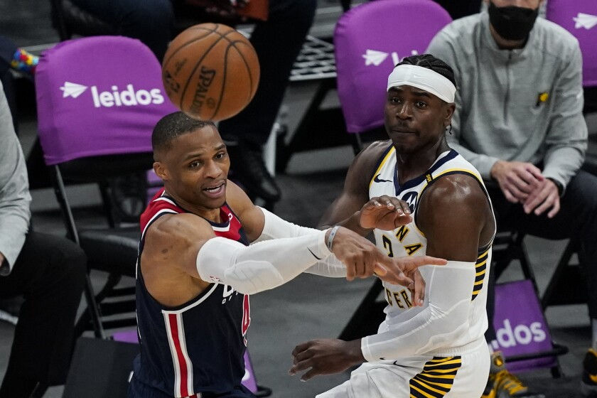 Washington Wizards guard Russell Westbrook (4) passes the ball as he is guarded by Indiana Pacers guard Aaron Holiday (3) during the second half of a basketball game, Monday, May 3, 2021, in Washington. (AP Photo/Alex Brandon)