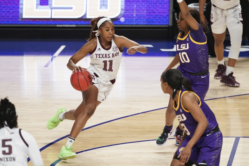 Texas A&M guard Kayla Wells (11) drives to the basket against LSU guard Ryann Payne (10) during the first half of an NCAA college basketball game Friday, March 5, 2021, during the Southeastern Conference tournament in Greenville, S.C. Texas A&M won 77-58. (AP Photo/Sean Rayford)