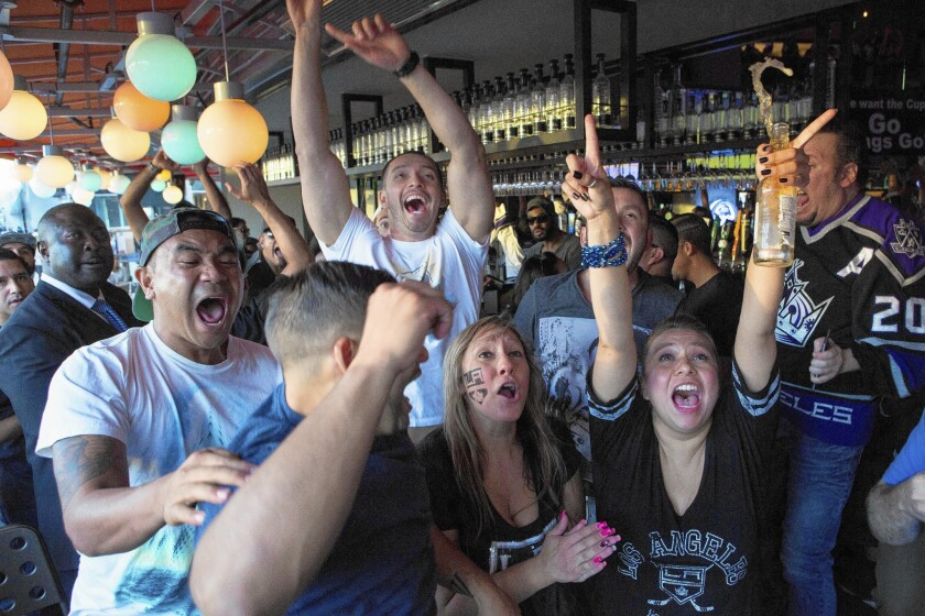 Fans cheer at L.A. Live as the Kings tied the score against the Rangers in the third period Friday.