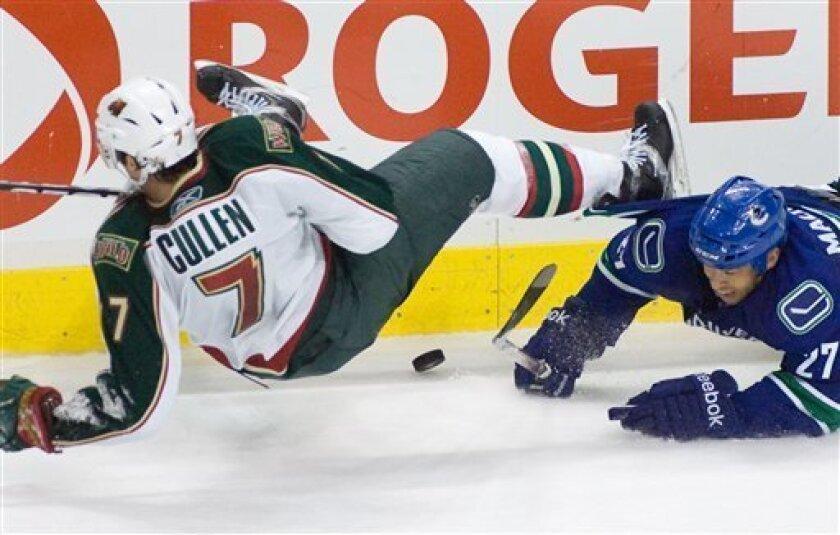 Vancouver Canucks' Manny Malhotra (27) knocks over Minnesota Wild's Matt Cullen (7) to clear the puck during the final minutes of third period during an NHL hockey game Monday, March 14, 2011, in Vancouver, British Columbia. Vancouver won 4-2. (AP Photo/The Canadian Press, Geoff Howe)