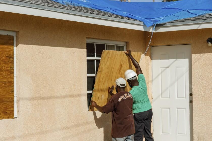 Residentes cubren una ventana con un tablón de madera antes de la llegada del huracán Isaías, en el vecindario de Heritage, en Freeport, en la isla de Gran Bahama, Bahamas, el 31 de julio de 2020. (AP Foto/Tim Aylen)