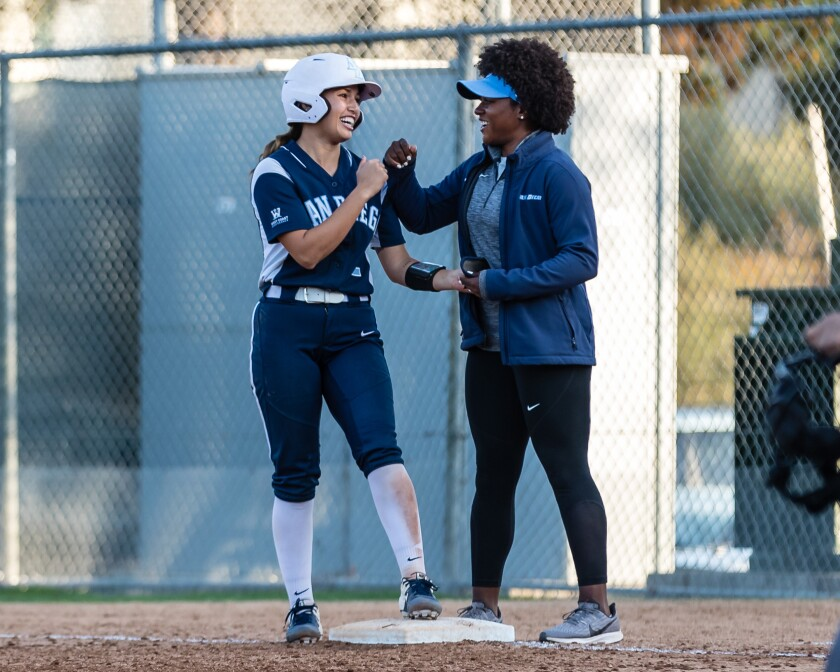 New USD softball coach MJ Knighten (right) gives Madison Casiano a fist bump last season.