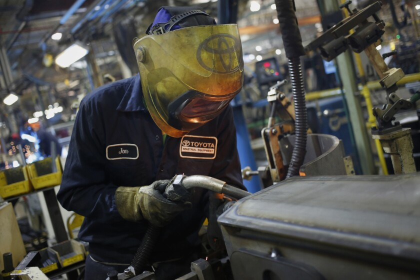 A worker welds components on the assembly line at a Toyota factory in Indiana.