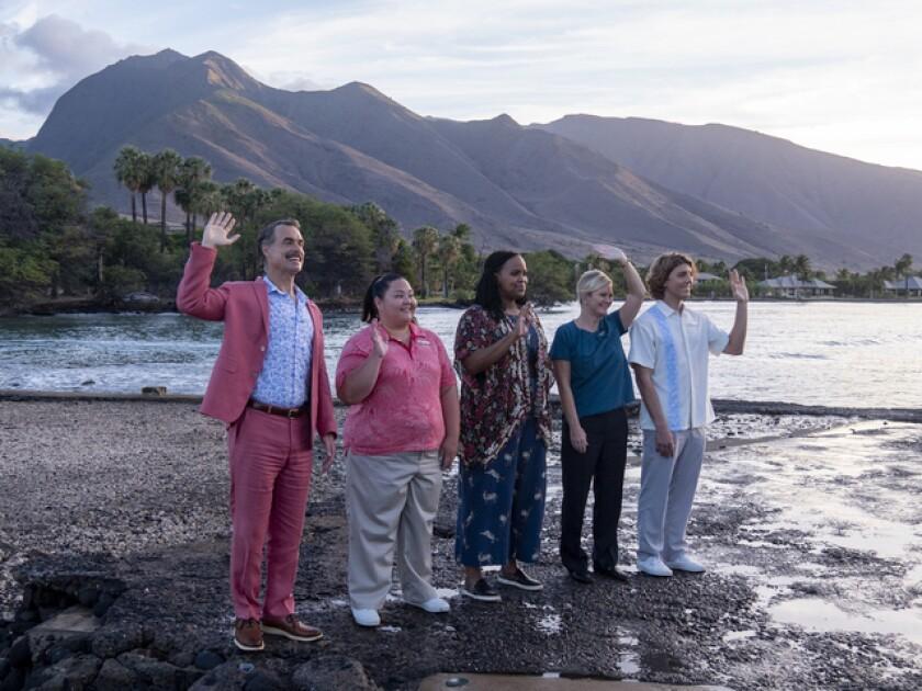 El personal del resort de lujo saluda a los huéspedes desde la playa
