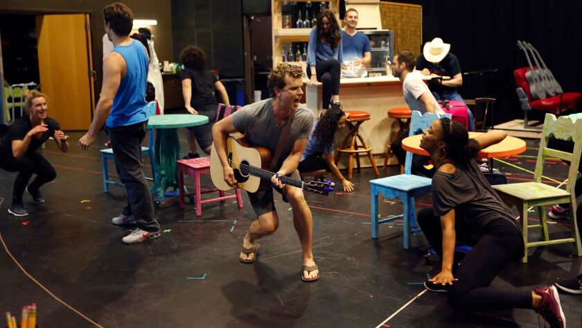 "Paul Alexander Nolan (center) and cast mates rehearse a number from ""Escape to Margaritaville"" at La"