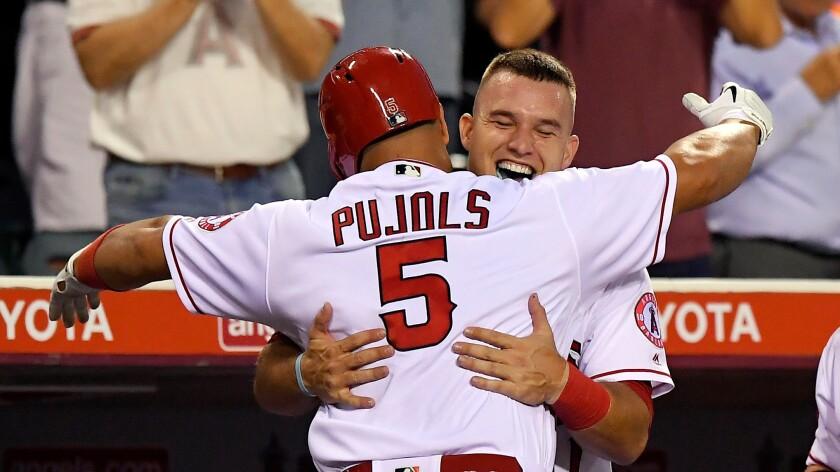Mike Trout, right, congratulates Albert Pujols, who hit a home run against Cincinnati on Monday.