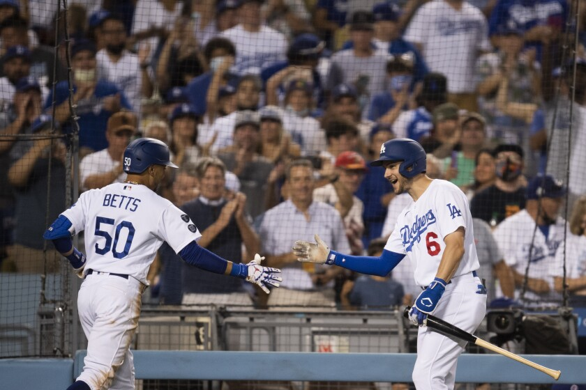 Mookie Betts celebrates with Dodgers teammate Trea Turner after hitting a three-run home run.