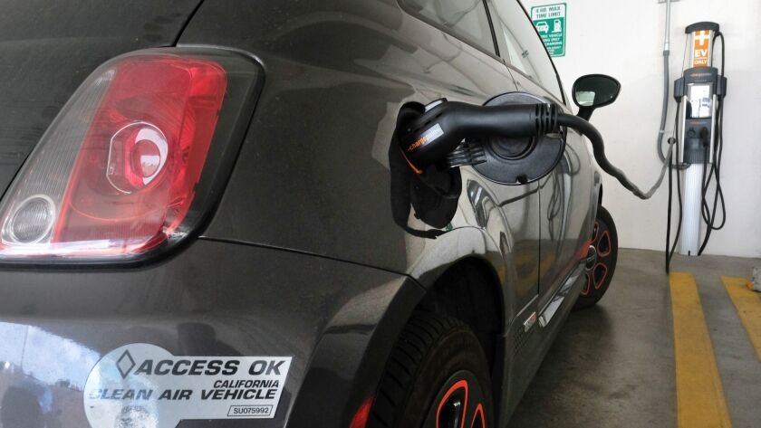 FILE - This April 25, 2016 file photo photo shows an electric Fiat plugged into a charging station i