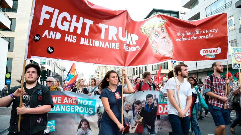 Protesters hold a banner as they take part in a demonstration againt the US president in Brussels o