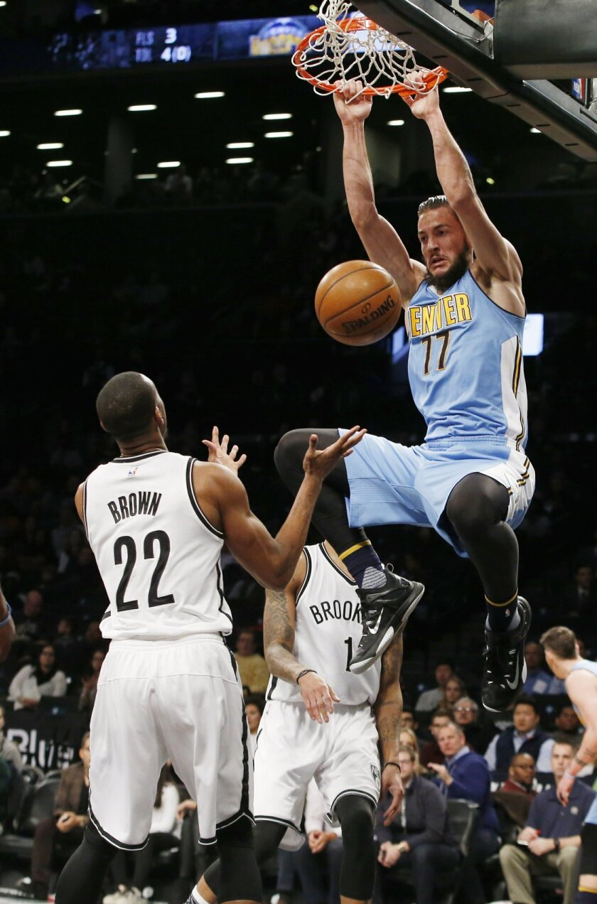 Denver Nuggets center Joffrey Lauvergne (77) dunks in front of Brooklyn Nets guard Markel Brown (22) in the first half of an NBA basketball game, Monday, Feb. 8, 2016, in New York. (AP Photo/Kathy Willens)