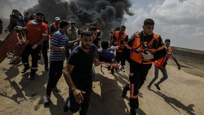 GAZA CITY, GAZA -- MONDAY, MAY 14, 2018: Medical units carry away a wounded Palestinian shot by Isra