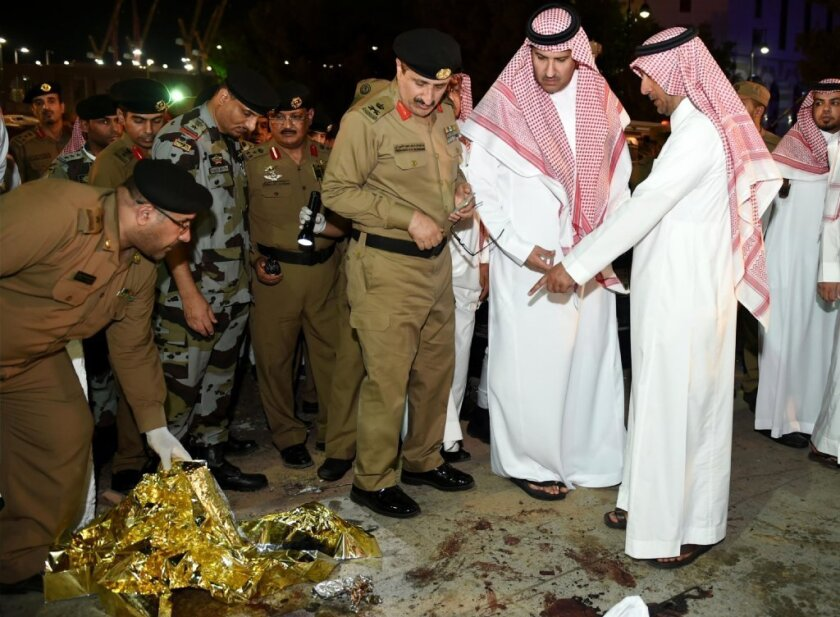 Faisal bin Salman bin Abdulaziz, governor of Medina province, center, and security officers look at blood stains on the ground after a suicide attack near one of Islam's holiest sites, the Prophet's Mosque in Medina, on Monday.