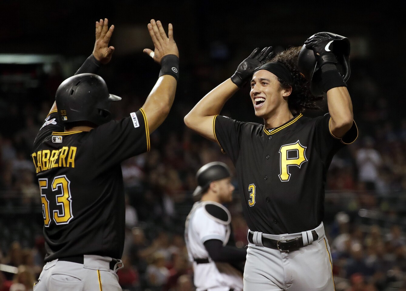Pittsburgh Pirates' Cole Tucker celebrates his two-run home run with Melky Cabrera (53) during the eighth inning of the team's baseball game against the Arizona Diamondbacks, Tuesday, May 14, 2019, in Phoenix. (AP Photo/Matt York)