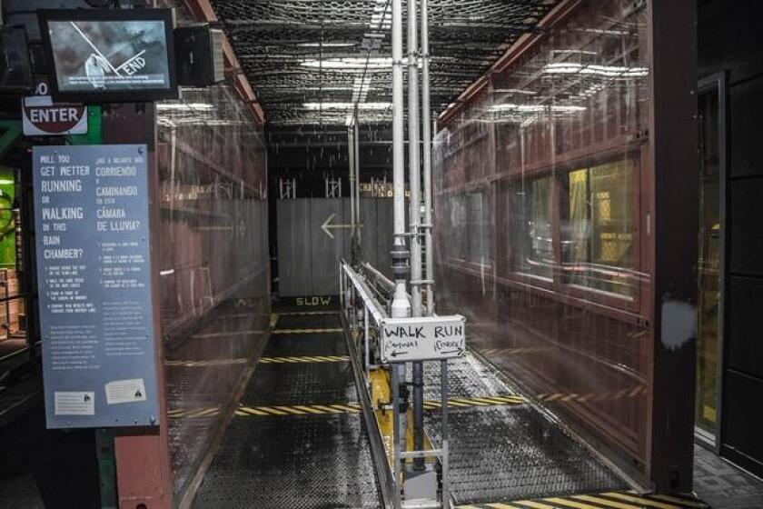 The MythBusters exhibit's Rain Chamber lets visitors test the validity of the myth: 'You stay drier walking through a rainstorm than running through it;' on display through Sept. 3, 2018 at Fleet Science Center in Balboa Park, San Diego.