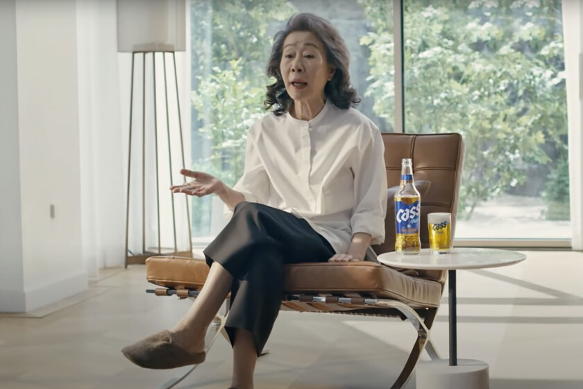"""In this image made from an undated commercial video, South Korean actor Youn Yuh-jung """"Minari"""", 74 years old, sits in the beer company Oriental Brewery's latest advertising campaign. Named """"Time to be Real,"""" the beer advertisement video starts as the camera closes in on the Oscar-winning actress's face, saying, """"For someone like me to be on a beer ad, the world has gotten so much better."""" (Oriental Brewery via AP)"""
