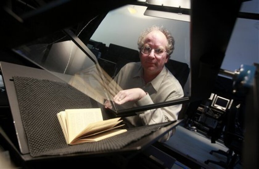 In this May 3, 2010 photo, Internet Archive digital librarian Brewster Kahle poses for a photograph in front of a book scanner at the Internet Archive office in San Francisco, Monday, May 3, 2010. Using money from foundations, libraries, corporations and the government, the organization has hired h
