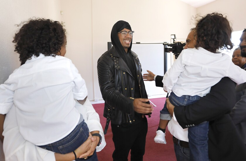 The People's Alliance For Justice, a civil rights group, opened its headquarters with a ribbon-cutting ceremony that included Assemblywoman Shirley Weber, celebrity Nick Cannon, shown here greeting families, and the Rev. Shane Harris, the group's founder.
