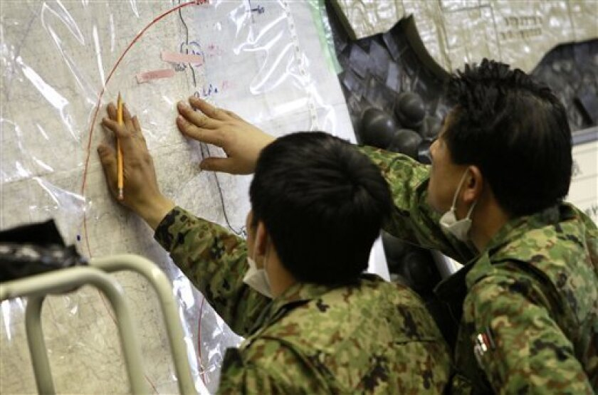 Japan's Defense Ministry officials plot possibly radioactive affected areas on a map at the emergency rescue headquarters monitoring leaked radiation from the Fukushima nuclear facilities damaged by last week's major earthquake and following tsunami, Wednesday, March 16, 2011, in Fukushima city, Fu