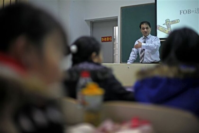 In this Tuesday, Dec. 1, 2009 photo, economist Ilham Tohti, from China's predominantly Muslim Xinjiang region speaks to students at the Central Nationalities University in Beijing, China. His weekly lectures are a kind of high-wire act and he has been put under house arrest dozens of times over the past decade for criticizing how China runs his homeland and treats his people. Yet Tohti is not a separatist or even a political dissident. He's a Communist Party member and a teacher at a top Chinese university who sees himself as a bridge between Hans and Uighurs. That the government has so far refused to endorse his middle road and work with him shows how difficult it is to resolve differences between the party and its restive Uighurs and Tibetans. (AP Photo/Elizabeth Dalziel)