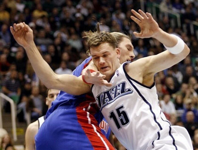 Utah Jazz forward Matt Harpring (15) gets fouled hard by Detroit Pistons forward Walter Herrmann (5), of Argentina, during the first half of their NBA basketball game Saturday, Jan.  10, 2009 in Salt Lake City. (AP Photo/Steve C. Wilson)