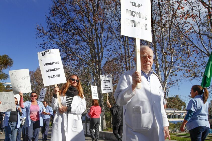 Dr. Steve Cowgill, right,  and Dr. Caroline Paterno march with other union representatives Tuesday at UCSD.