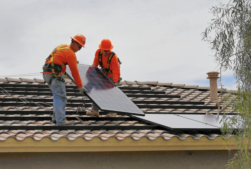 Electricians install solar panels on a roof for Arizona Public Service company in Goodyear, Ariz. in July of 2015.